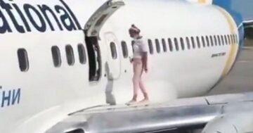 Repülőgép szárnyra mászó nő